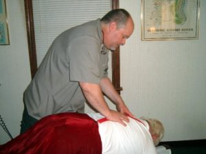 Chiropractor Dr. Miller performing an adjustment on Santa at the annual Christmas party
