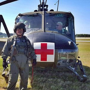 Chiropractor Dr. Miller standing in front of a Huey helicopter